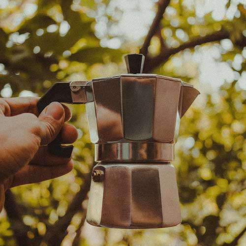 A side-view of a Moka Pot with a hand holding it up and some trees in the background.