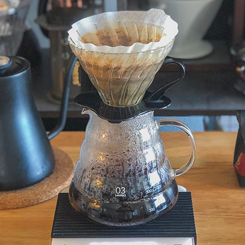 A glass Hario V60 sitting on a glass Hario coffee server with coffee inside.