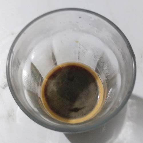 A close up of a latte glass with some coffee with some crema inside.