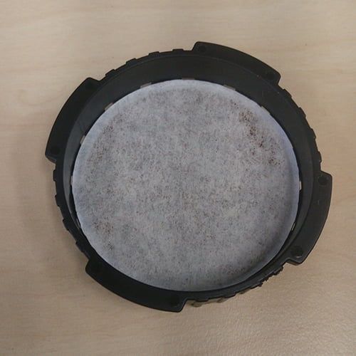 A used AeroPress Coffee Maker filter inside the filter cap